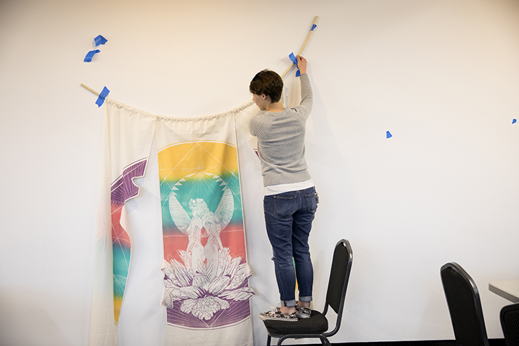 Image of student standing on chair, hanging artwork