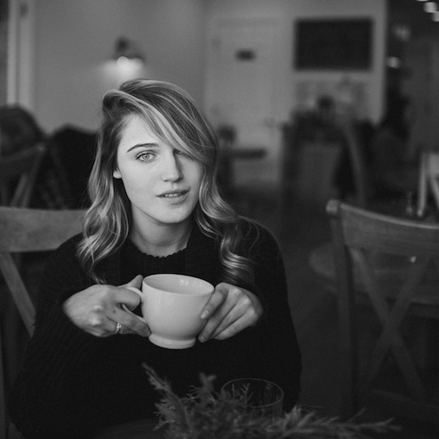 Taylor holding coffee cup seated at cafe table