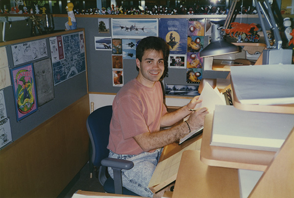Tony smiles up at camera while working at animation desk
