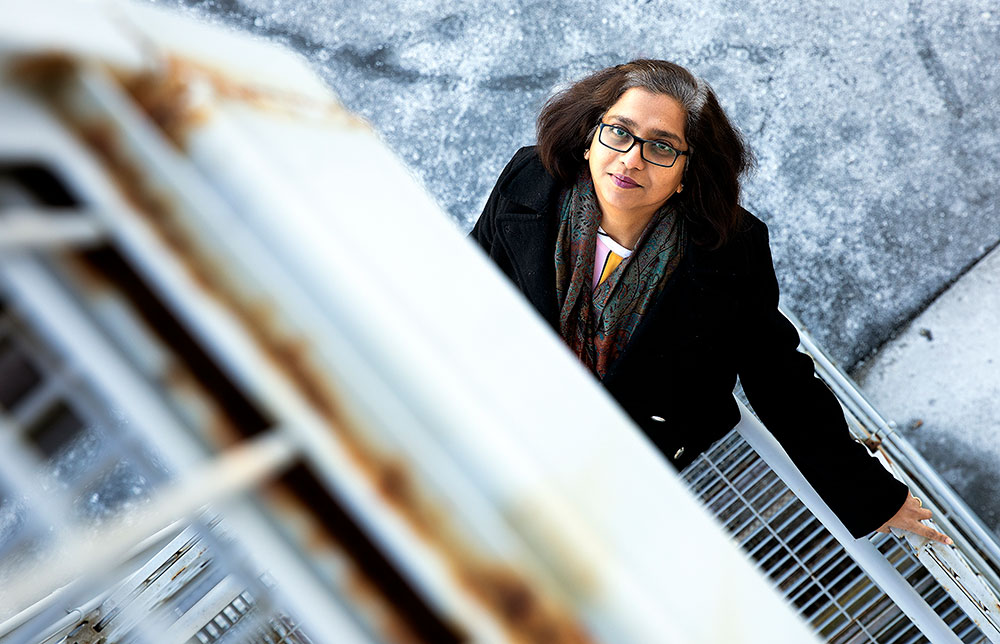 Photo of Sapna looking up from industrial stairwell