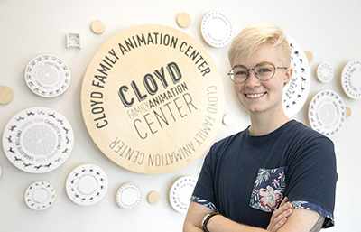 Erica Eppert (Illustration, 2018) in front of the Cloyd Family Animation Center donor wall she designed.