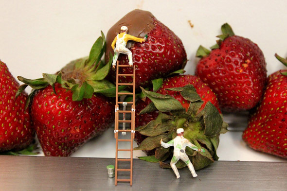 Photo of artwork, small sculptures of people working in coating strawberries with chocolate. Miniature