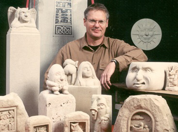 Advertising & Graphic Design, George poses for camera sitting among several of his sculpted works. Smiling, in a brown buttoned shirt, against a black backdrop.