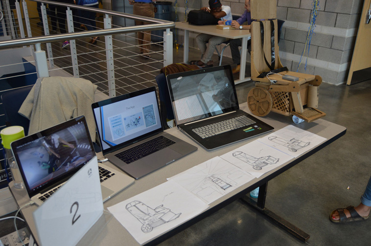 Life at CCAD, Table containing three laptops and multiple rendered images of concepts for autonomous mobility wheelchairs