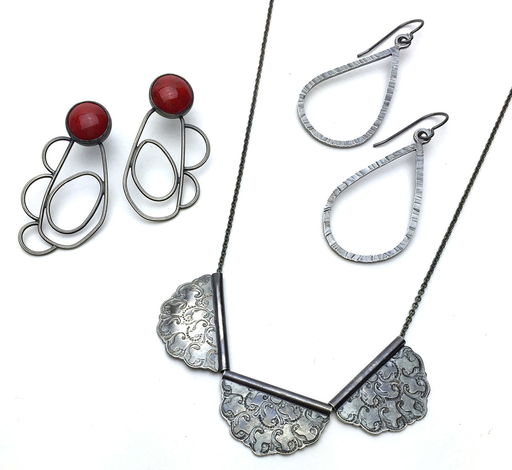 Contemporary Crafts, Image of necklace with three petal shaped pendants, pair of metal tear drop earrings, and pair of red earrings with metal petals on a white background