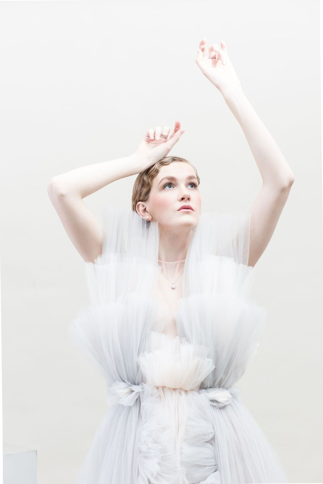 Fashion Design, Model in pastel tulle garment by Jennie Moon posing, looking up towards light with arms raised