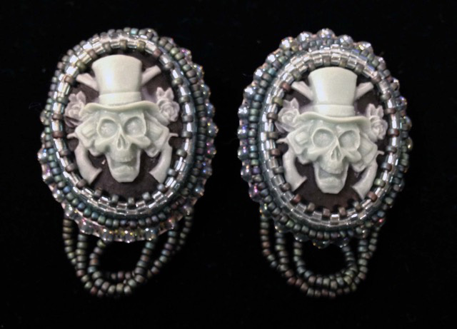 Master of Fine Arts, Image of Victorian Inspired earrings with skulls in top hats with guns and roses on a black backdrop
