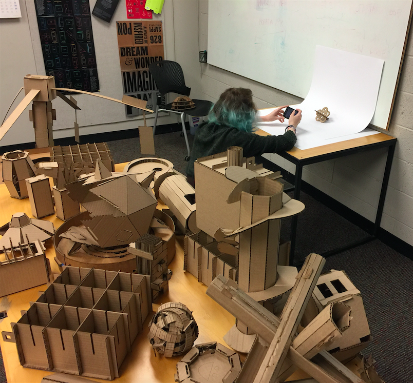 Animation,  student photographs small cardboard piece while surrounded by larger cardboard structures on a nearby table