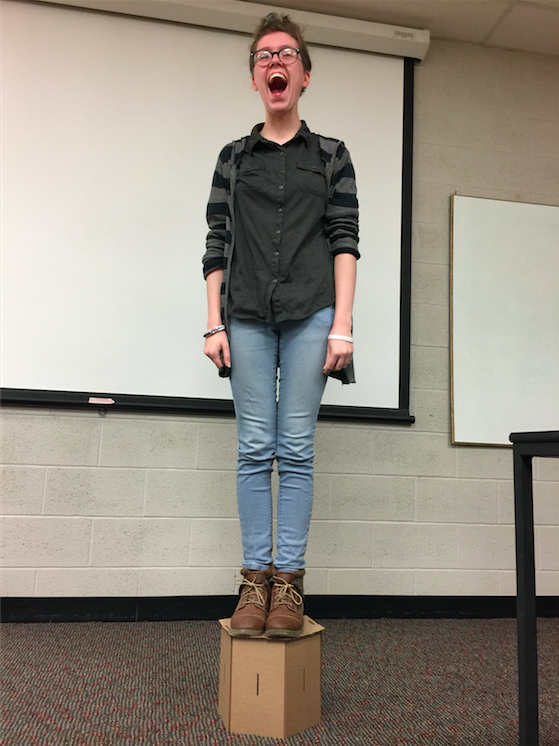 Animation, student stands on cardboard structure in classroom