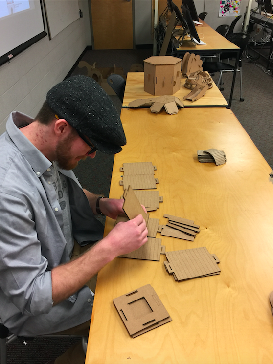 Animation, student works at table to piece cardboard structure together