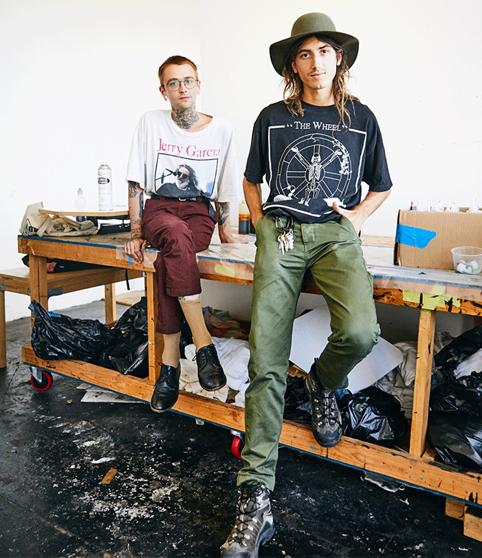 Fine Arts, Alix Ross and Elijah Funk pose for photo sitting on a workshop table