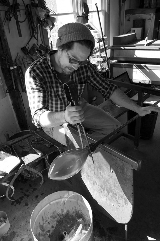 Fine Arts, Black and white image of matthew working with blown glass and tools, surround by glass blowing equipment