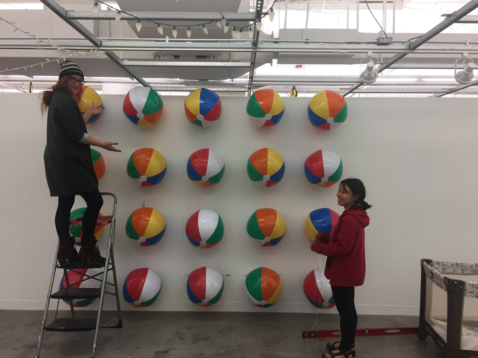 Master of Fine Arts, Two students construct white gallery wall of beach balls, one standing on step ladder