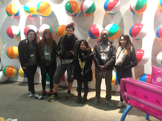 Master of Fine Arts, team of six students pose in front of wall of beach balls with pool float lounge chair in corner