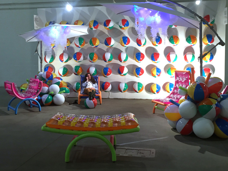 Master of Fine Arts, Student poses talking on cell phone in rubber pool chair in front of white gallery wall of colorful beachballs