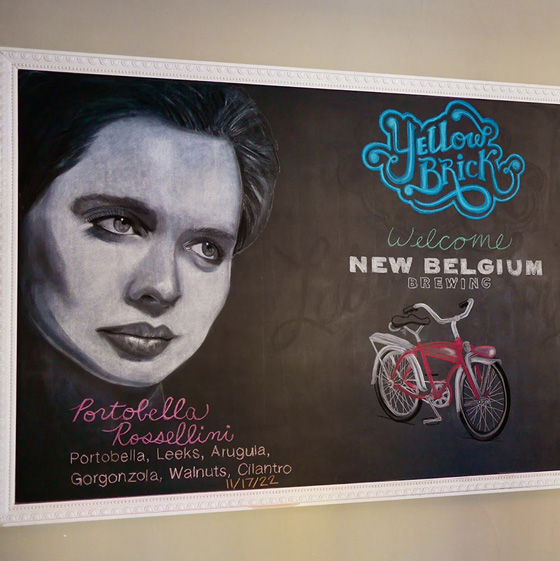 Fine Arts, Chalk Portrait of Isabella Rossellini next to Yellow Brick logo and red bicycle