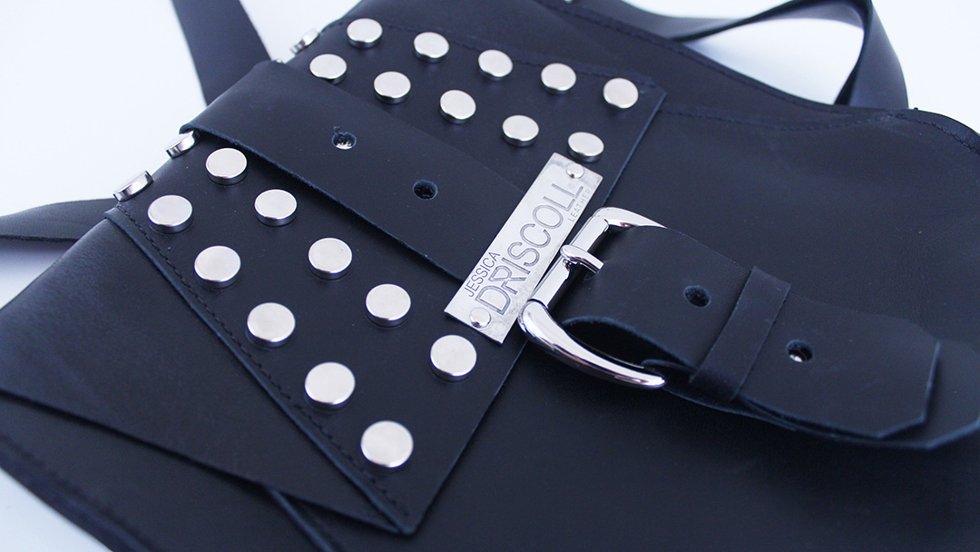 Fashion Design, Close up Image of black hand bag with silver hardware and name plate on white background