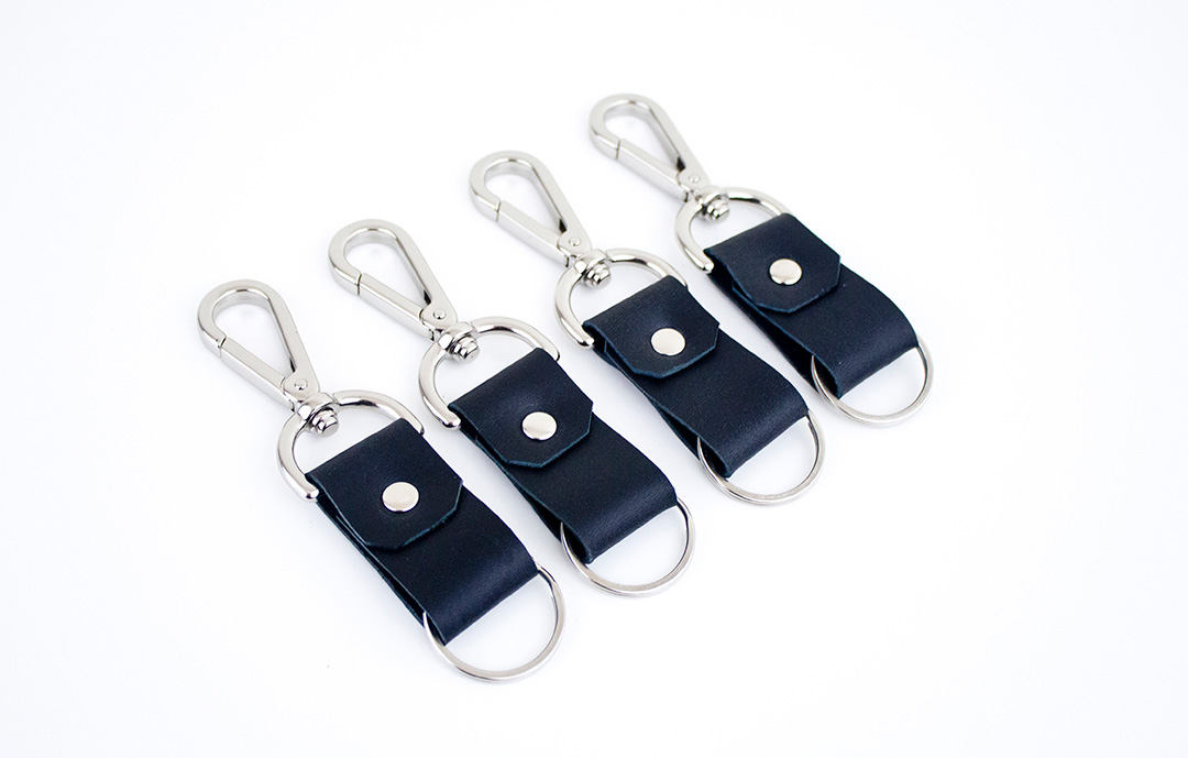 Fashion Design, Image of black of four leather key rings with silver hardware on white background