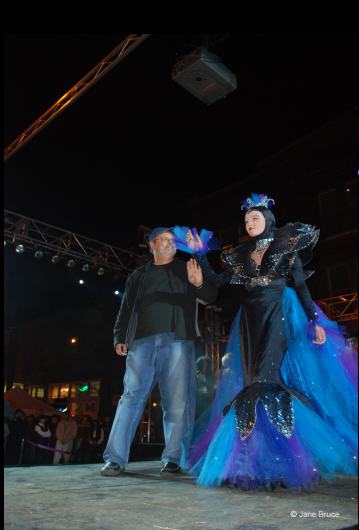 Fashion Design, Kevin Kerr's original design for HighBall Halloween, Kevin with model in form fitting black and blue dress with shoulder pads and blue train