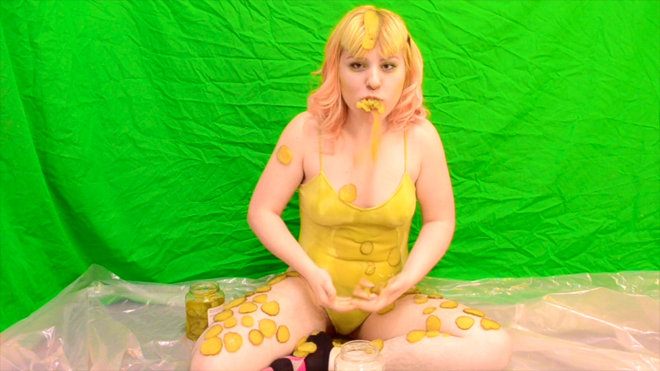 Image of person in yellow body suit sitting in front of a green screen covered in pickles with pickles hanging out of mouth