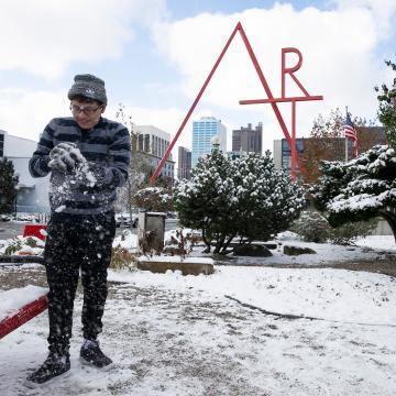Photo of student seeing and feeling snow for the first time in front of the red Art sculpture