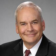 Headshot of Robert E. Morrison, Jr. in black suit jacket with white shirt and red tie, against a gradated gray background