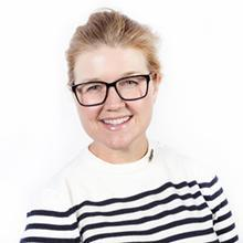 Headshot of Jeni Britton Bauer in white and black striped shirt with black glasses, smiling, against a white background