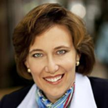 Headshot of Susan D. Rector in black and white jacket with multicolored patterned scarf against a blurred background.