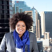 Headshot of Tanisha Robinson in gray suit jacket over white shirt and blue scarf, against a backdrop of city buildings in Columbus.